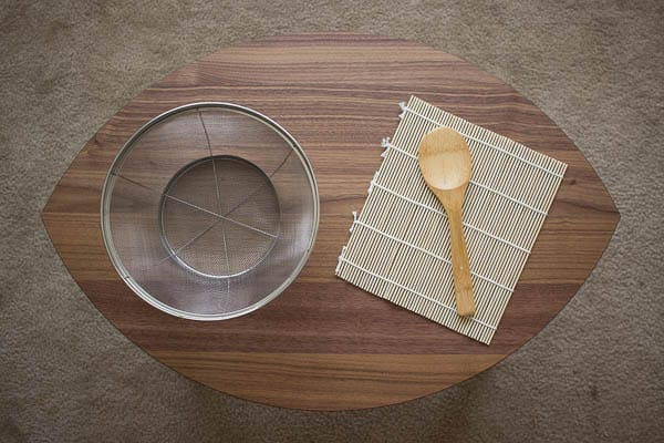 A stainless-steel colander, a bamboo rolling mat, a wooden rice spatula